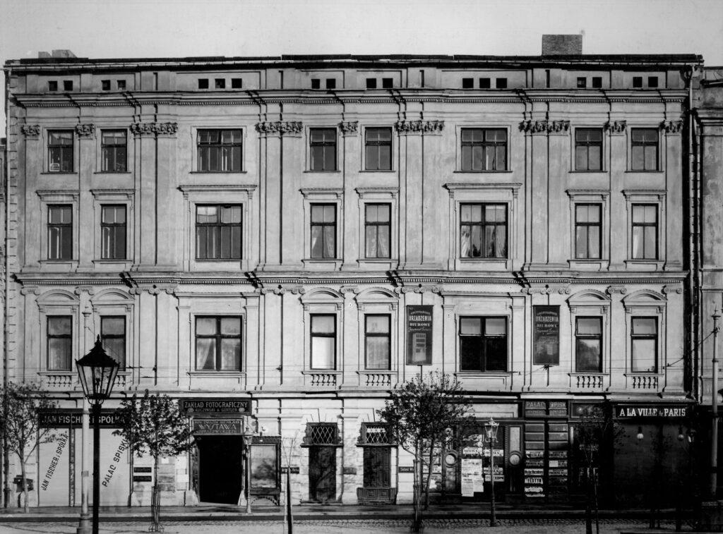 Fotografia czarno-biała przedstawiająca elewację frontową trzypiętrowego, ośmioosiowego budynku, naparterze liczne szyldy ireklamy, napierwszym planie, polewej latarnia uliczna