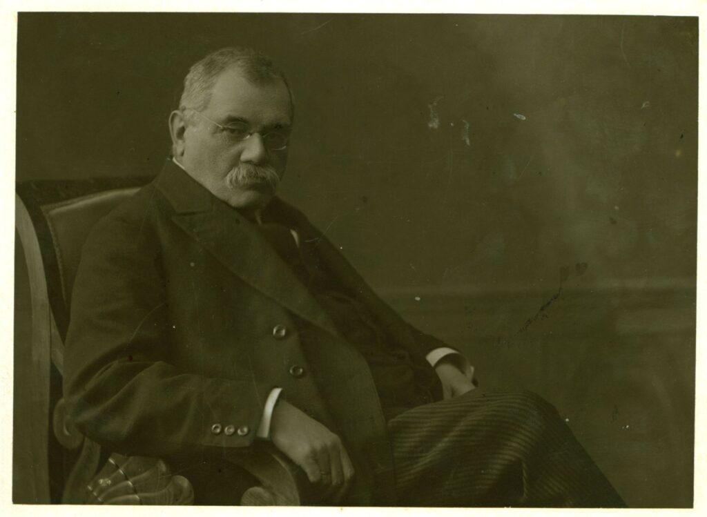 Fotografia czarno-biała, portret atelierowy przedstawiający starszego mężczyznę zwąsami izokularami, siedzącego nafotelu biedermeier