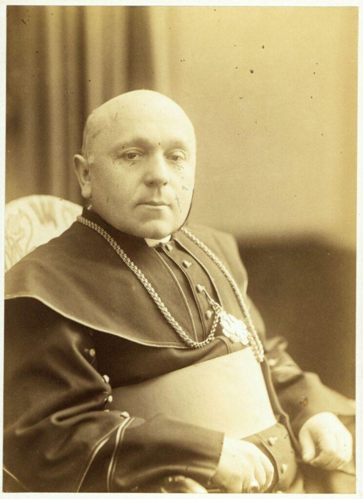 Fotografia czarno-biała, portret atelierowy przedstawiający starszego mężczyznę, duchownego, siedzącego nafotelu