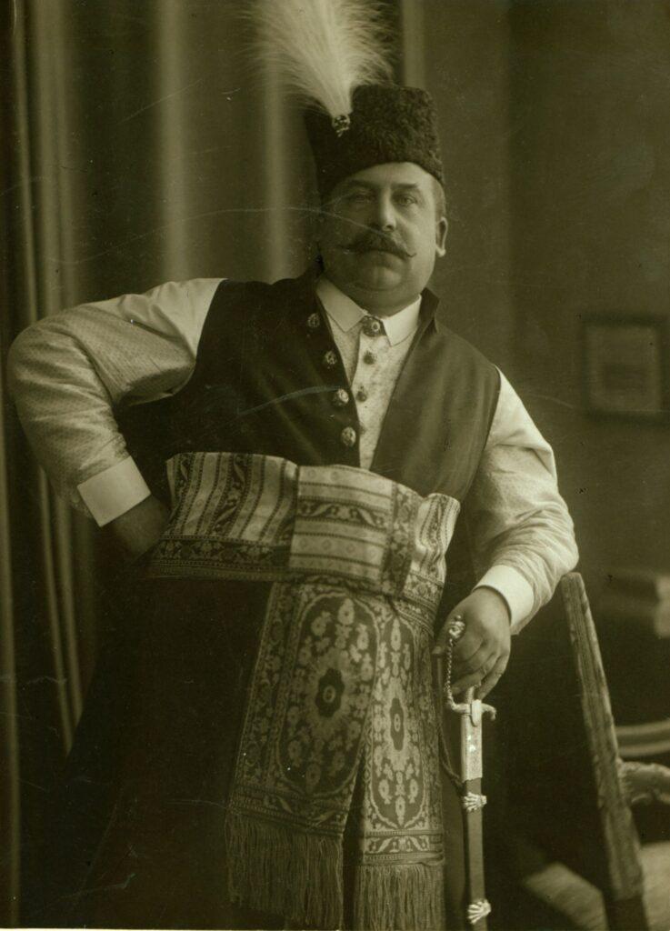 Fotografia czarno-biała, portret atelierowy przedstawiający mężczyznę wśrednim wieku ubranego wstrój polski zpasem kontuszowym, zkołpakiem nagłowie ikarabelą