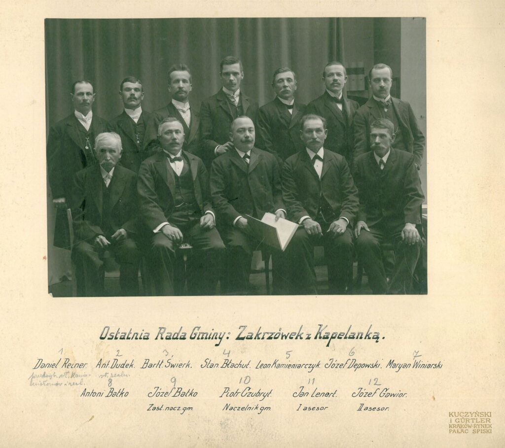 Fotografia czarno-biała, portret atelierowy przedstawiający dwunastu mężczyzn, wdwóch rzędach, członków ostatniej Rady Gminy Zakrzówek zKapelanką