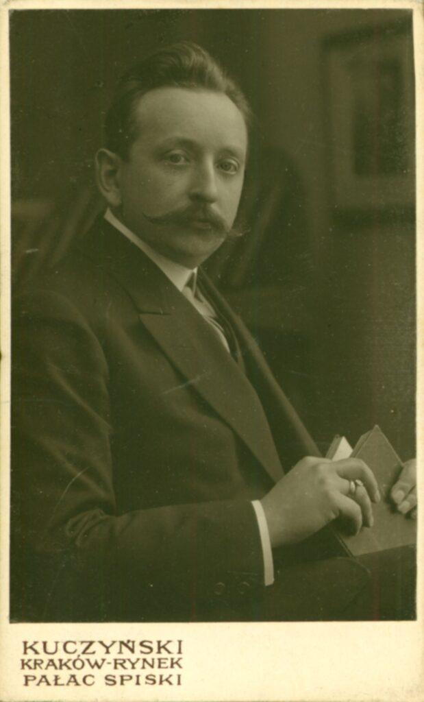 Fotografia czarno-biała, portret atelierowy przedstawiający młodego mężczyznę zwąsami izksiążką wręce