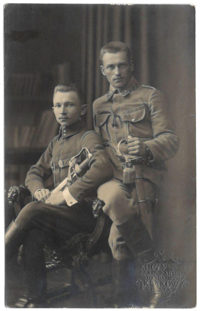 Fotografia czarno-biała, portret atelierowy przedstawiający dwóch młodych mężczyzn wwojskowym mundurze zszablami