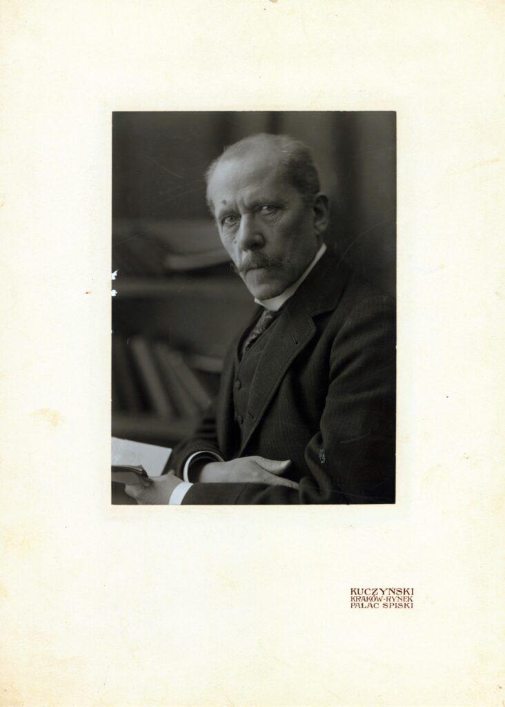 Fotografia czarno-biała, portret atelierowy przedstawiający starszego mężczyznę zwąsami