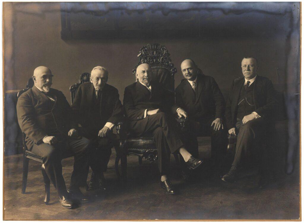 Fotografia czarno-biała wykonana wjednym zpomieszczeń magistratu, przedstawiająca pięciu mężczyzn siedzących nafotelach, członków Tymczasowy Zarząd Miasta Krakowa zokresu 19 VII 1924–2 VI 1926