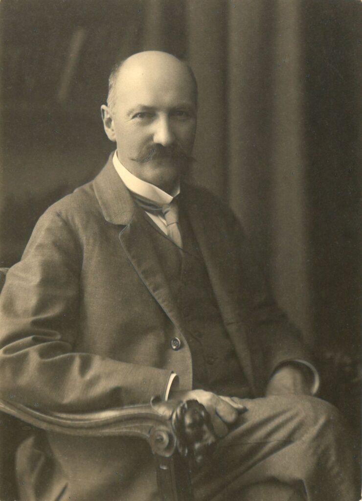 Fotografia czarno-biała, portret atelierowy przedstawiający starszego mężczyznę siedzącego nafotelu