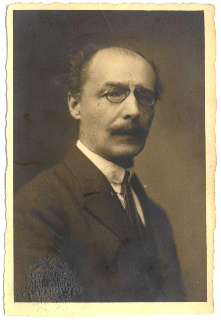Fotografia czarno-biała, portret atelierowy przedstawiający starszego mężczyznę wokularach