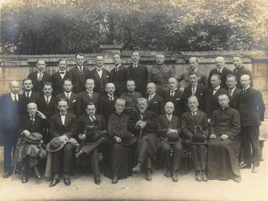 Fotografia czarno-biała, portret przedstawiający trzydziestu jeden mężczyzn ustawionych wtrzech rzędach, natle murowanego ogrodzenia ikoron drzew